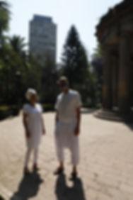 Mujer y hombre parados lado a lado viendo hacia arriba vestidos de blanco cerca de edificio antiguo con columnas griegas
