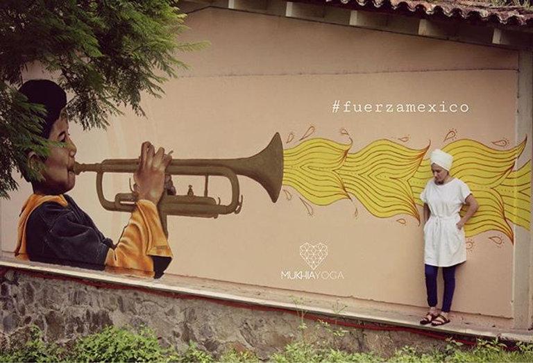 Mujer con turbante recargada contra pared con mural de un niño moreno tocano una trompeta que saca fuego benevolo amarillo.