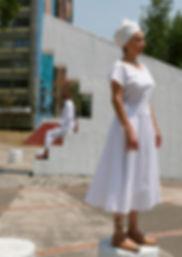 Mujer con vestido blanco y turnate en primer plano hombre en segundo plao sobre estructura geométrica blanca y edificios al fondo