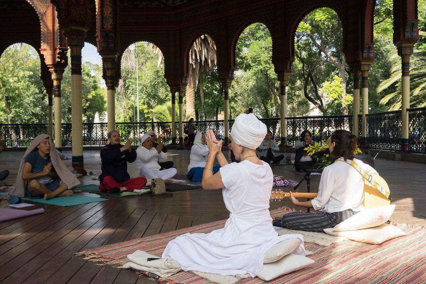 Maestra de Kundalini Yoga en frente de alumnos realizando meditación con las palmas juntas