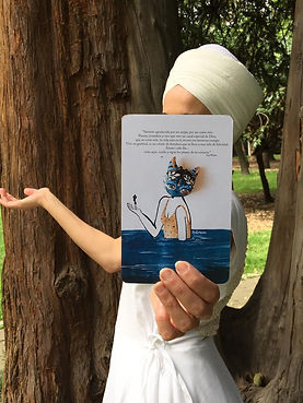 Mujer mostrando ilustración de criatura humana con cabeza de gato en agua azul marino.