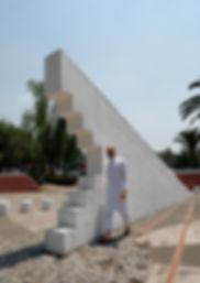 Hombre con barba vestido de blanco junto a una estructura geométrica blanca