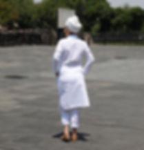 Mujr vetida de blanco con turbant de espaldas mirando hacia la izquierda