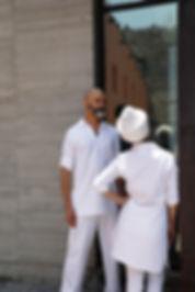 Hombre viendo a la distancia derecha de la camara parado a la izquierda de mujer con turbante dando espalda a camara viendo su reflejo en ventana larga hacia arriba vestidos de blanco.