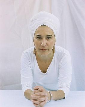 Mujer con turbante y ropa blanca viendo directo a camara recargada sobre superficie blanca con sus codos y manos entrelazadas hacia adelante