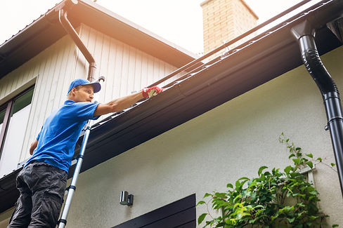 man on ladder cleaning house gutter from