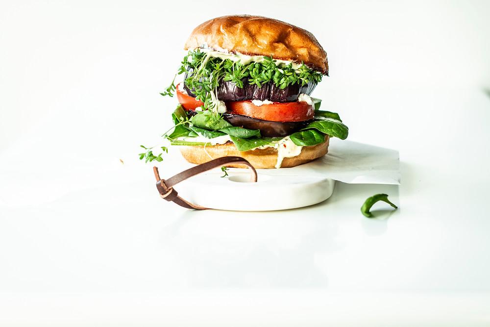 Vegetarischer Burger mit Tomate und Spinat. Das schnelle und einfache Rezept für diesen vegetarischen Bohnen Auberginen Burger und viele weitere köstliche vegetarische Feierabend Rezepte findest du im Wochenmagazin von MOE'S QUICK & EASY FOOD