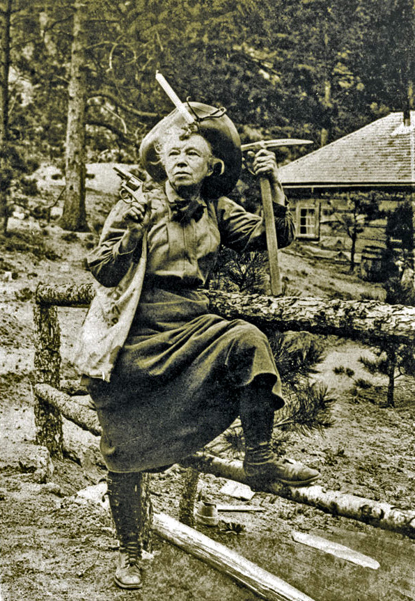 Captain Ellen Jack with loaded sixshooter, miner's pick, and miner's candle at her High Drive cabin in the mountains above Colorado Springs. Circa 1900.