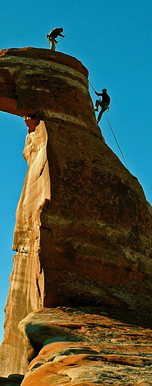 Climbing a sandstone spire by Arches National Park.
