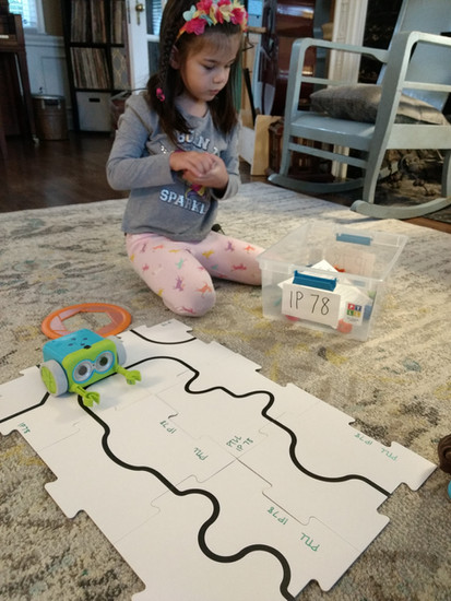 Child sits on rug at home, looking down, next to Botley coding robot