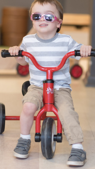 Child on red tricycle, wearing sunglasses, looking at camera and smiling