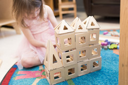 Child sits behind a castle made of wooden magnetic tiles