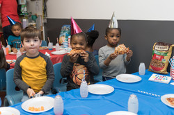 Three children sit at table wearing party hats, eating pizza, looking at camera