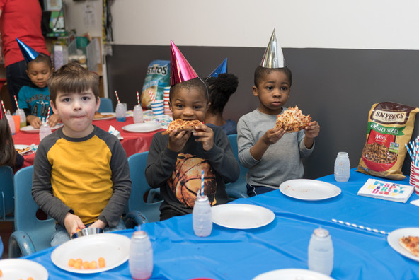 Three children sit at table wearing party hats, looking at camera, eating pizza