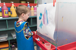 Child in art room, facing away from camera, painting on an easel blue, pink, white shapes