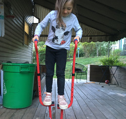 Outside on porch, child stands on Walkaroo balance stilts, looks down in concentration