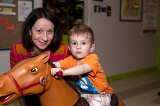 Adult, smiling, and child on rocking horse look at camera