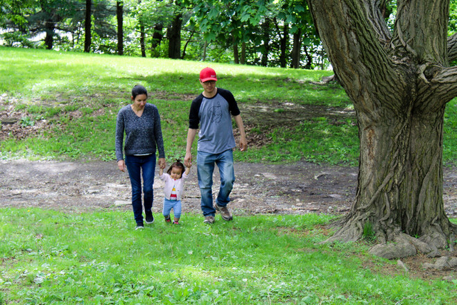 Outdoors, two adults and a child walk in grass next to tree, holding hands with child in center