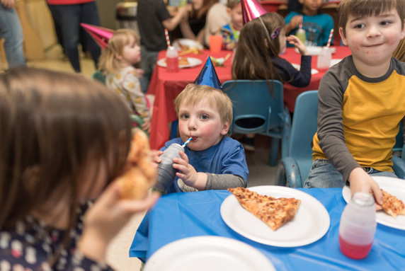 Child sitting at table, with party hat, drinking juice, with plate of pizza