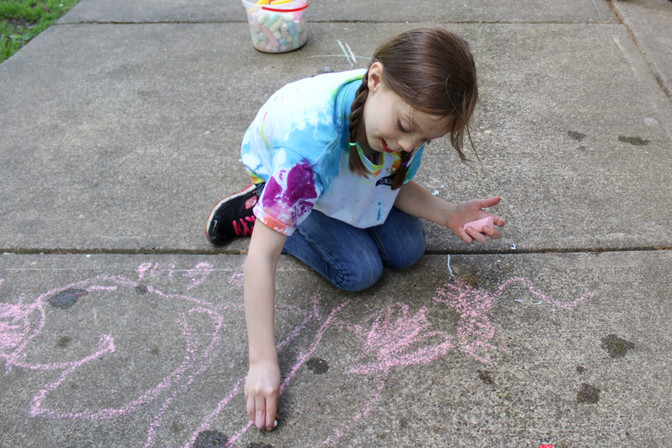 Child sits on knees outside, on concrete, smiling, looking down, drawing on ground with pink chalk