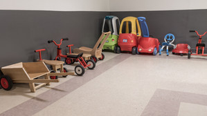 PTLL interior, with cars, bikes, ride-on toys against wall