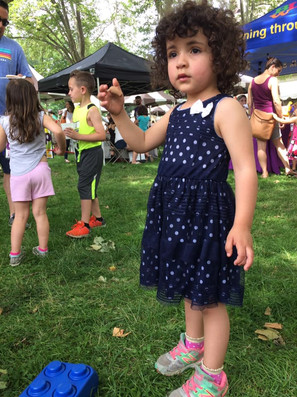 Child outside at an event, raising hand and looking past the camera