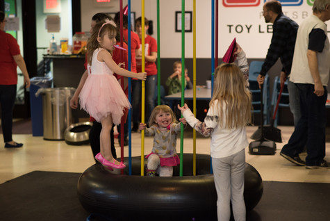 Three children with party hats and noisemaker play on Jungle Jumparoo