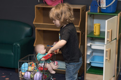 Child pushing play shopping cart with baby doll and play food in it