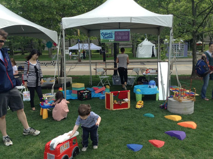 Outside in grass, canopy above water table, large firetruck and other toys, adults and children play