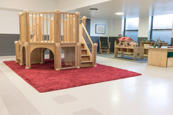 Toy library interior, large wooden play structure and dolls, dinosaurs in background