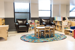 PTLL interior, reading and puzzle area with large chairs, small table/chairs, rack/shelf of books
