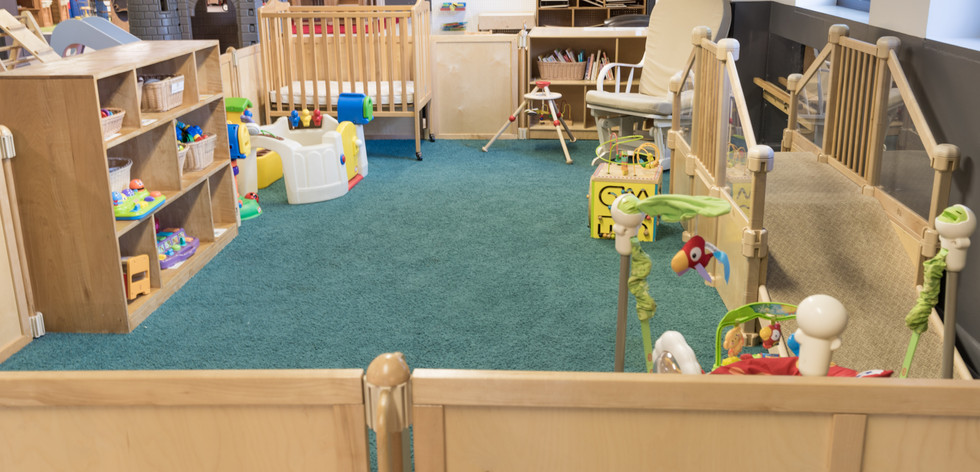 PTLL interior, gated infant area, showing a shelf of toys, crib, rocking chair