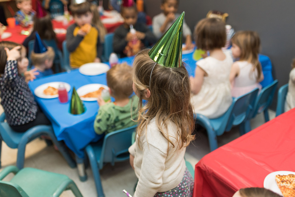 Children sit at tables and eat, in foreground is back of one child with green party hat