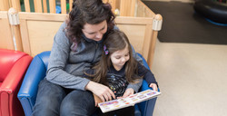 Parent and child in a small blue chair together, reading a book