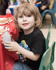 Child holding a juice drink looks at camera and smiles