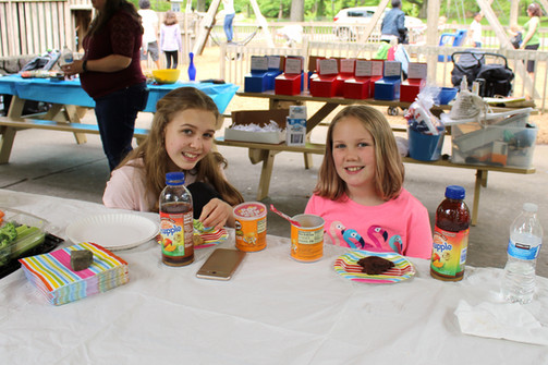 Two child sit at picnic table, smiling and looking at camera, with Pringles and drinks