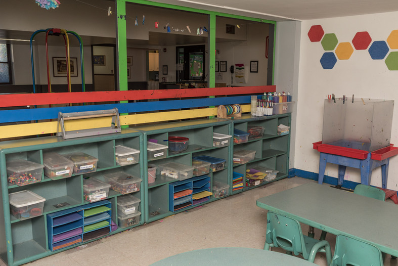 Art room, shot of tables and easel with long row of shelves holding art supplies