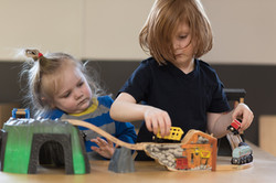 Child playing with wooden trains and bridges while another child watches
