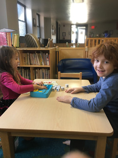Two children sit at table with Boogle Jr. game, one smiles at camera