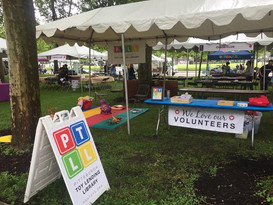 Outdoors at an event, PTLL sign in foreground, table under canopy next to mat with toys