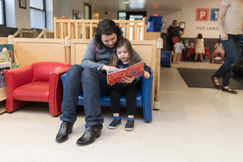 Adult and child together in blue chair reading a picture book