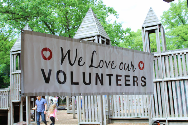 Wooden castle playground behind banner that says We love our volunteers