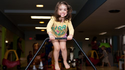 Child jumping on trampoline, looking at camera and smiling