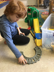 Indoor, child on floor, looking down, putting together track in Little Tikes train toy
