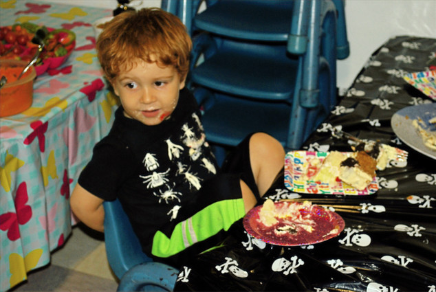 Child sits at table with skull table cover, with two plates of cake