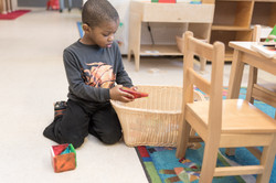 Child on floor next to woven basket, reaching in and holding one magnetic tile