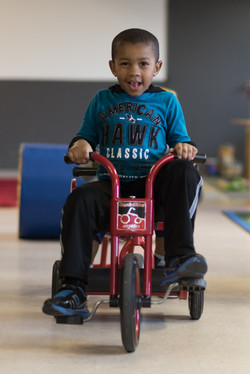 A child with a large grin sits, looking at the camera, on a red tricycle