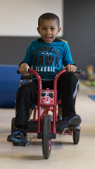Child on red tricycle, looking at camera and smiling