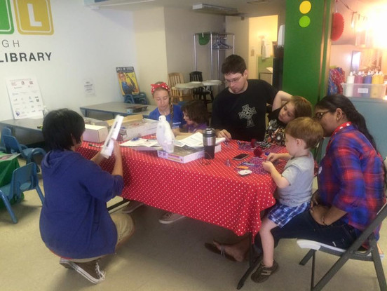 Inside PTLL, adults and children sit around a table in front area, working on an art project