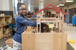 Child plays with a wooden dollhouse in the toy library, smiles at camera